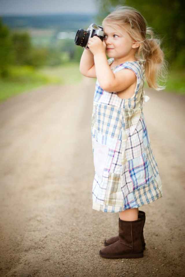 girl with blonde hair and wearing blue and white plaid dress and capturing picture during daytime